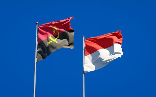 Mooie nationale vlaggen van indonesië en angola samen op blauwe hemel