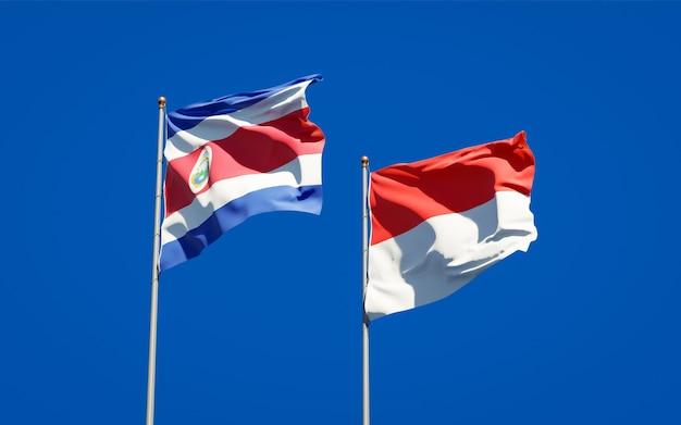 Mooie nationale vlaggen van indonesië en costa rica samen op blauwe hemel
