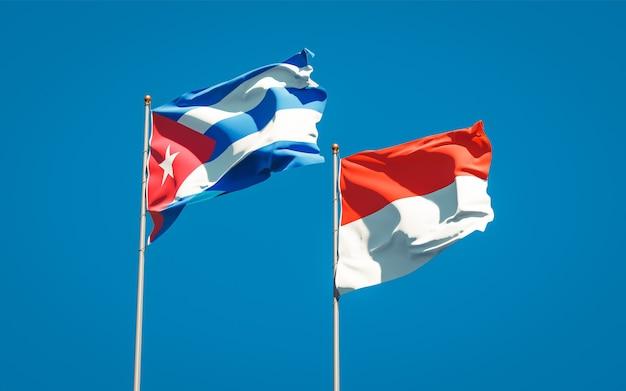 Mooie nationale vlaggen van indonesië en cuba samen op blauwe hemel