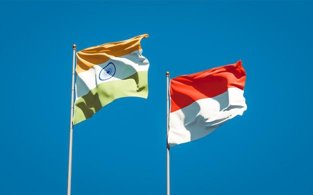 Mooie nationale vlaggen van indonesië en india samen op blauwe hemel