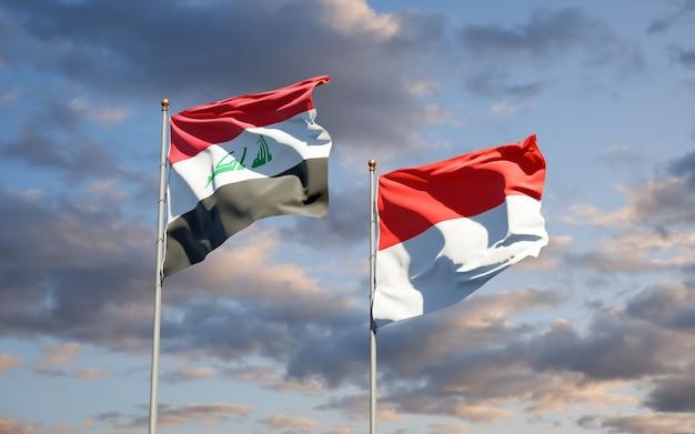 Mooie nationale vlaggen van irak en indonesië samen op blauwe hemel