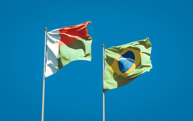 Mooie nationale vlaggen van madagaskar en brazilië samen op blauwe hemel