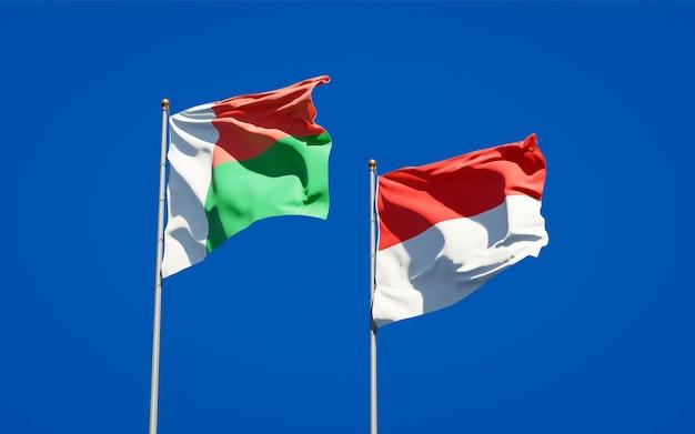 Mooie nationale vlaggen van madagaskar en indonesië samen op blauwe hemel