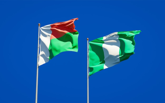 Mooie nationale vlaggen van madagaskar en nigeria samen op blauwe hemel