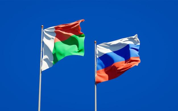 Mooie nationale vlaggen van madagaskar en rusland samen op blauwe hemel. 3d-illustraties