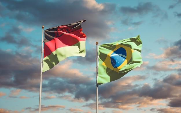 Mooie nationale vlaggen van malawi en brazilië samen op blauwe hemel