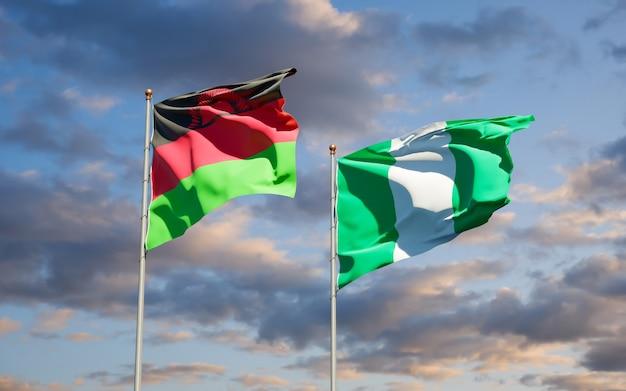 Mooie nationale vlaggen van malawi en nigeria samen op blauwe hemel