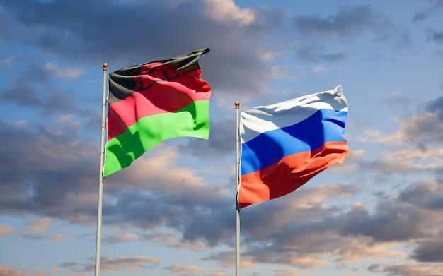 Mooie nationale vlaggen van malawi en rusland samen op blauwe hemel. 3d-illustraties
