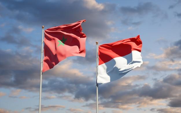 Mooie nationale vlaggen van marokko en indonesië samen op blauwe hemel
