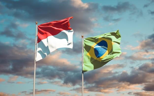 Mooie nationale vlaggen van monaco en brazilië samen op blauwe hemel