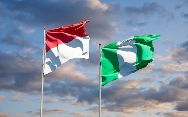 Mooie nationale vlaggen van monaco en nigeria samen op blauwe hemel