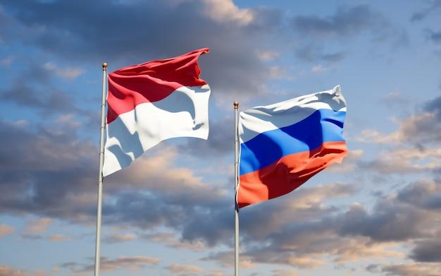 Mooie nationale vlaggen van monaco en rusland samen op blauwe hemel. 3d-illustraties