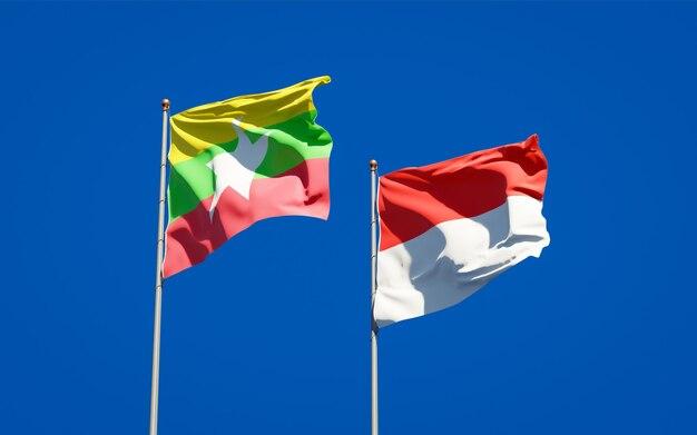 Mooie nationale vlaggen van myanmar en indonesië samen op blauwe hemel