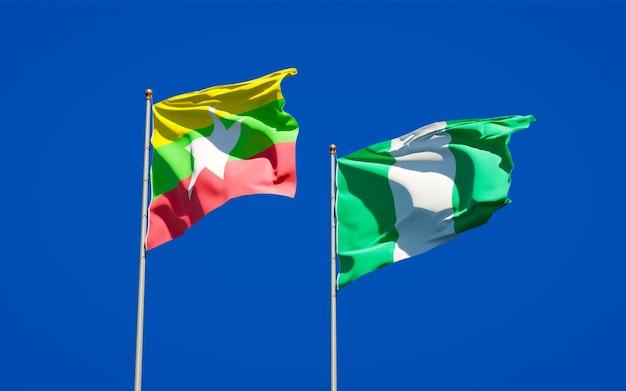 Mooie nationale vlaggen van myanmar en nigeria samen op blauwe hemel