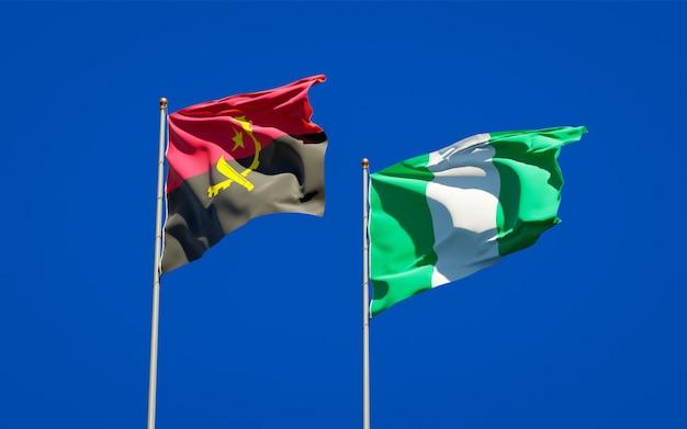 Mooie nationale vlaggen van nigeria en angola samen op blauwe hemel