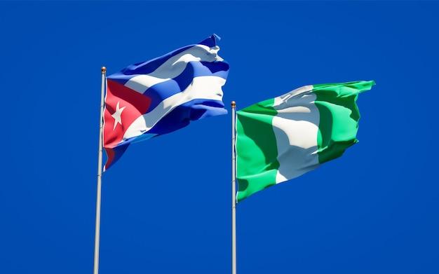 Mooie nationale vlaggen van nigeria en cuba samen op blauwe hemel