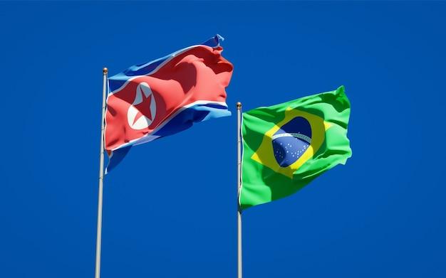 Mooie nationale vlaggen van noord-korea en brazilië samen op blauwe hemel