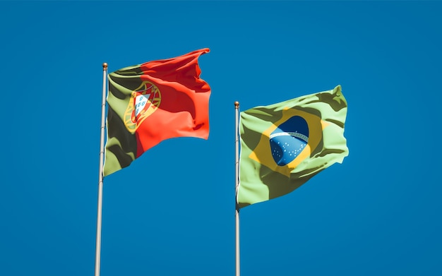 Mooie nationale vlaggen van portugal en brazilië samen op blauwe hemel