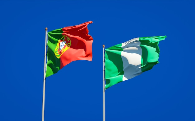 Mooie nationale vlaggen van portugal en nigeria samen op blauwe hemel