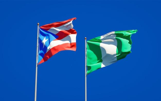 Mooie nationale vlaggen van puerto rico en nigeria samen op blauwe hemel
