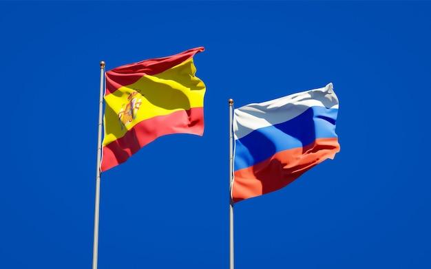 Mooie nationale vlaggen van spanje en rusland samen op blauwe hemel. 3d-illustraties