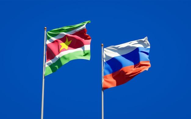 Mooie nationale vlaggen van suriname en rusland samen op blauwe hemel. 3d-illustraties