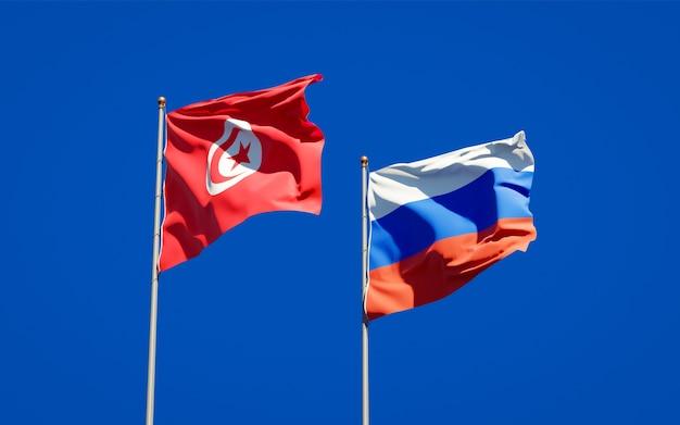 Mooie nationale vlaggen van tunesië en rusland samen op blauwe hemel. 3d-illustraties