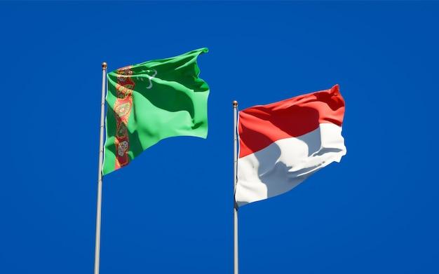 Mooie nationale vlaggen van turkmenistan en indonesië samen op blauwe hemel