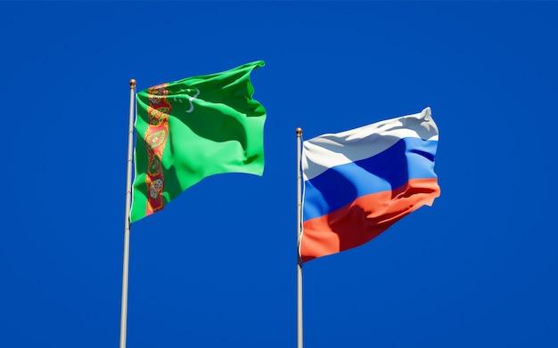 Mooie nationale vlaggen van turkmenistan en rusland samen op blauwe hemel. 3d-illustraties