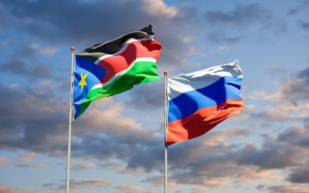Mooie nationale vlaggen van zuid-soedan en rusland samen op blauwe hemel. 3d-illustraties