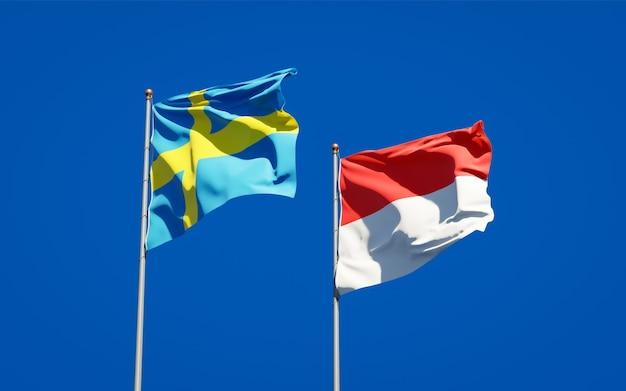 Mooie nationale vlaggen van zweden en indonesië samen op blauwe hemel