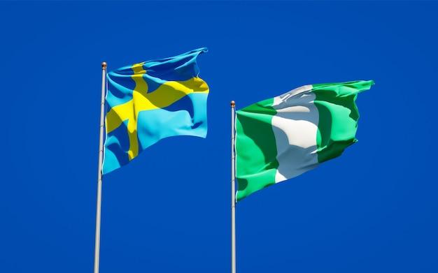 Mooie nationale vlaggen van zweden en nigeria samen op blauwe hemel