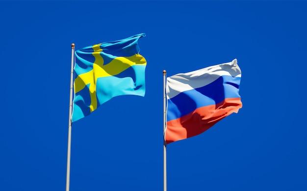 Mooie nationale vlaggen van zweden en rusland samen op blauwe hemel. 3d-illustraties