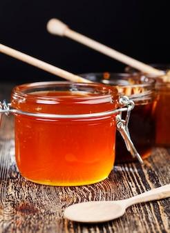Mooie natuurlijke honing van amberkleur, bijenhoning verzameld door honingbijen in het lente- en zomerseizoen, honing wordt verpakt in gerechten