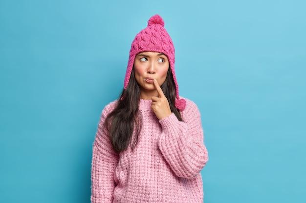 Mooie natuurlijke jonge aziatische vrouw draagt gebreide trui en muts houdt vinger in de buurt van lippen geconcentreerd opzij denkt na over plannen voor wintervakantie geïsoleerd over blauwe muur
