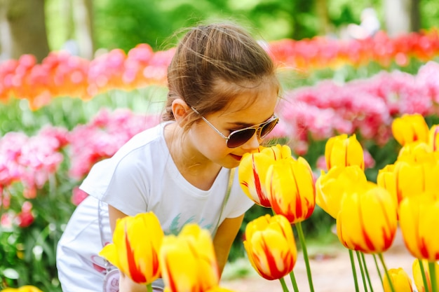Mooie nederlandse ruikende de tulpenbloem van het meisje op tulpengebieden. kind op tulpenbloemgebied in holland. kid in magische nederland landschap met tulpen veld in keukenhof. reizen en lente concept.