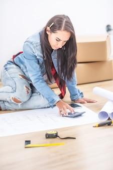 Mooie nieuwe vrouwelijke huiseigenaar zittend op een vloer omringd door blauwdrukken, met behulp van een rekenmachine.