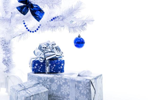 Mooie nieuwjaarscadeaus in zilverblauwe kleur staan onder de kerstboom op een witte achtergrond.
