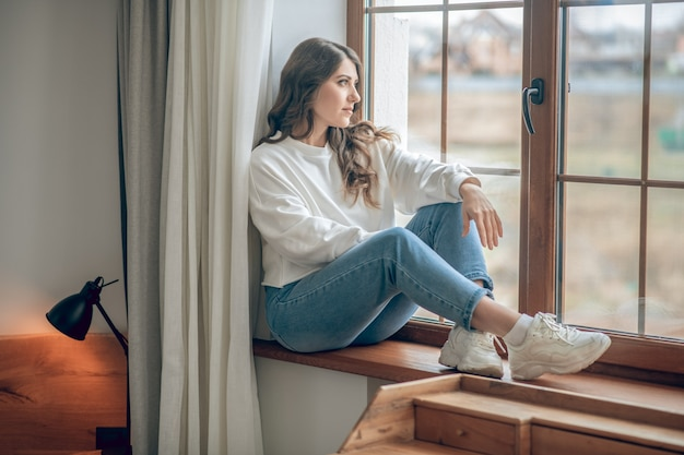 Mooie ochtend. mooie jonge langharige vrouw in een witte blouse die bij het raam zit