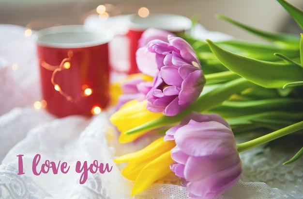 Mooie ochtend, twee kopjes koffie en een boeket felle tulpen. inscriptie ik hou van je.