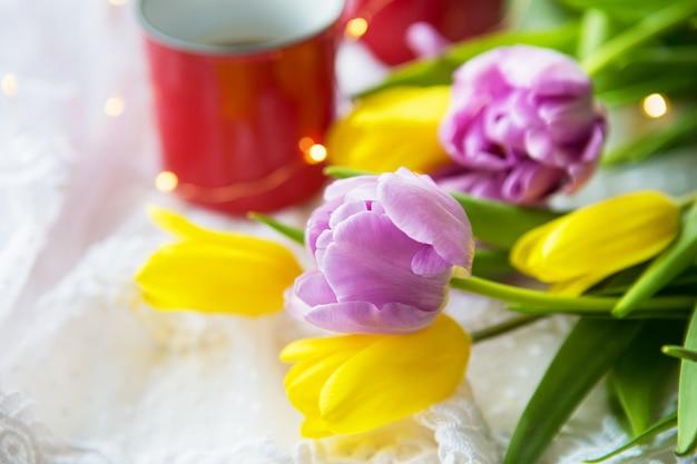Mooie ochtend, twee kopjes koffie en een boeket heldere en mooie tulpen. bloem close-up.