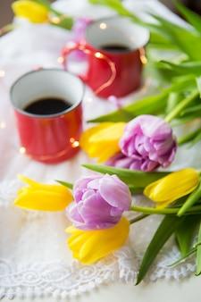 Mooie ochtend, twee kopjes koffie en een boeket heldere en mooie tulpen. detailopname.