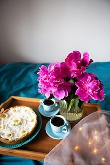 Mooie ochtend vanille cheesecake, koffie, blauwe kopjes, roze pioenrozen in een glazen vaas.