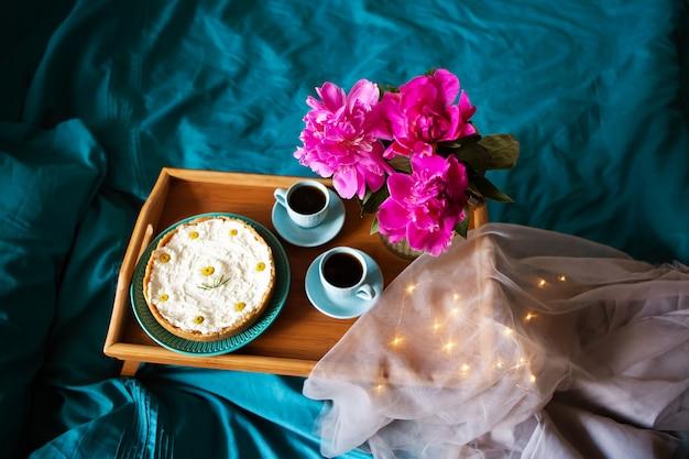 Mooie ochtend vanillekaastaart, koffie, blauwe kopjes, roze pioenrozen in een glazen vaas.