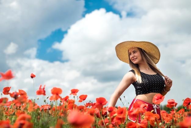 Mooie oekraïense in zwarte top en hoed geniet van een zonnige dag in het rode papaverveld