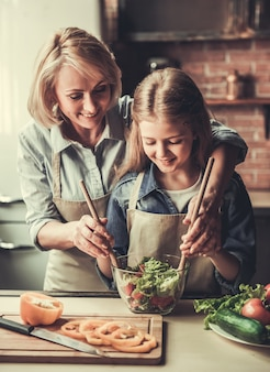 Mooie oma en kleindochter mengen salade.