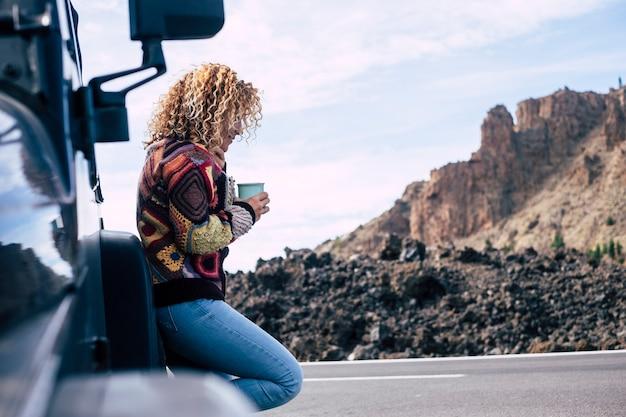 Mooie onafhankelijke krullende blonde blanke vrouw van middelbare leeftijd rust na een reis met haar off-road zwarte auto geparkeerd in de buurt van de straat.