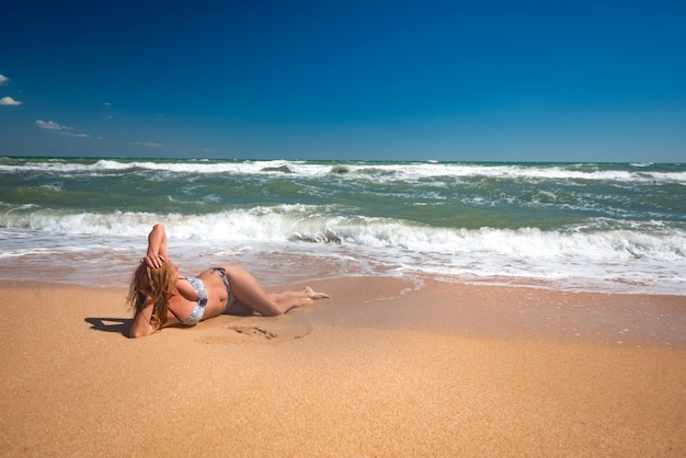 Mooie onbekende ontspannen jonge vrouw ligt aan een zandstrand en ontspant op de zee op een zonnige warme zomerdag