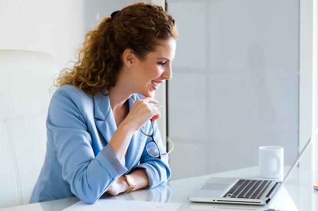 Mooie onderneemster die met haar laptop in het bureau werkt.