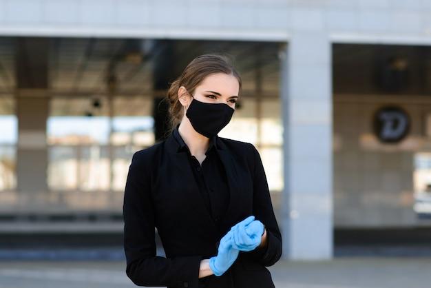 Mooie onderneemster in een zwart kostuum in een zwart medisch masker en handschoenen bij de stad in quarantaine en isolatie. pandemie covid-19. selectieve aandacht